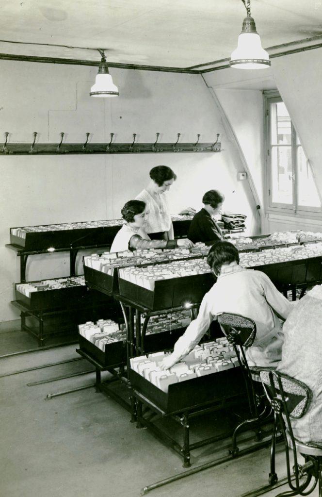 """Employées du service de la conservation des titres sur leur chaise Flambo """"roule-dactyle"""", Banque nationale de Crédit, vers 1930. Archives historiques BNP Paribas."""