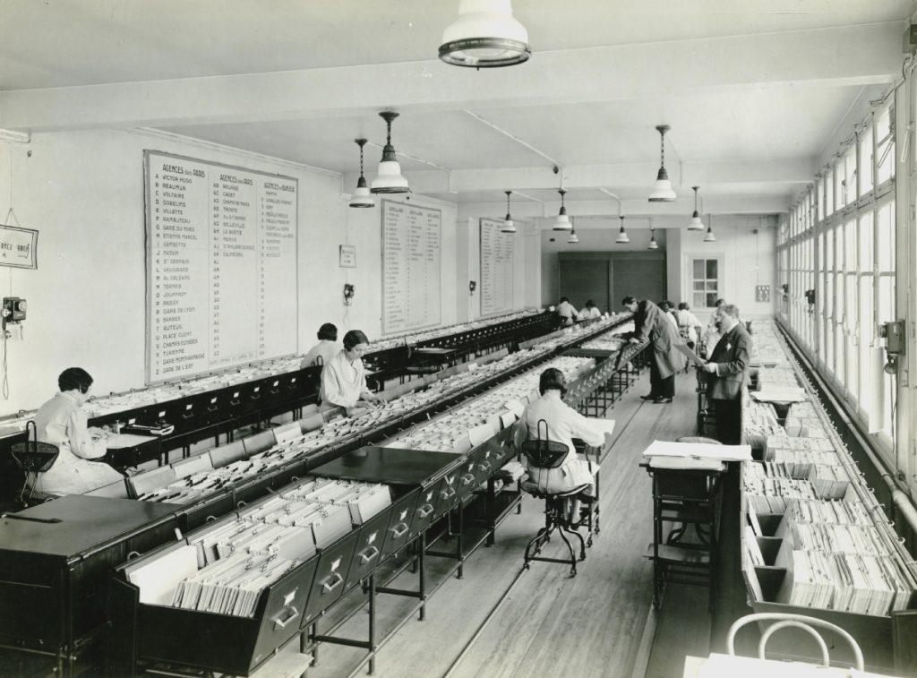 """Employées du service de la conservation des titres sur leur chaise flambo """"roule-dactyle"""", Banque nationale de Crédit, 1931. Archives historiques BNP Paribas."""