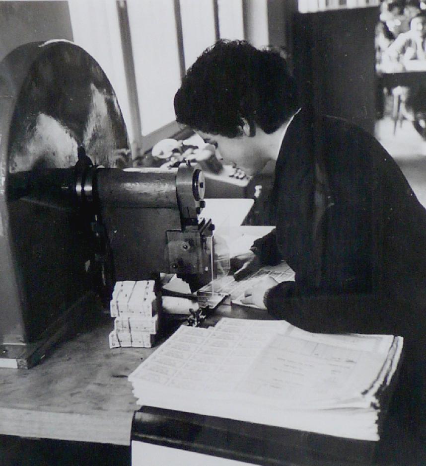Une couponnière détachant les coupons à la main, vers 1950. BNP Paribas, Archives historiques.