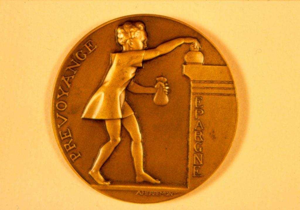 Prévoyance et épargne: une jeune fille apporte une bourse pour remplir sa tirelire posée sur un comptoir. Médaille gravée par Herbemont, 1920. Fédération nationale des Caisses d'épargne, documentation.