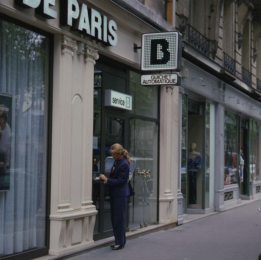 Les premiers guichets automatiques de banque GAB, 1984. BNP Paribas, archives historiques. Une cliente et sa conseillère au Concept Store, 2 place de l'Opéra, Paris, 2011. BNP Paribas, archives historiques.